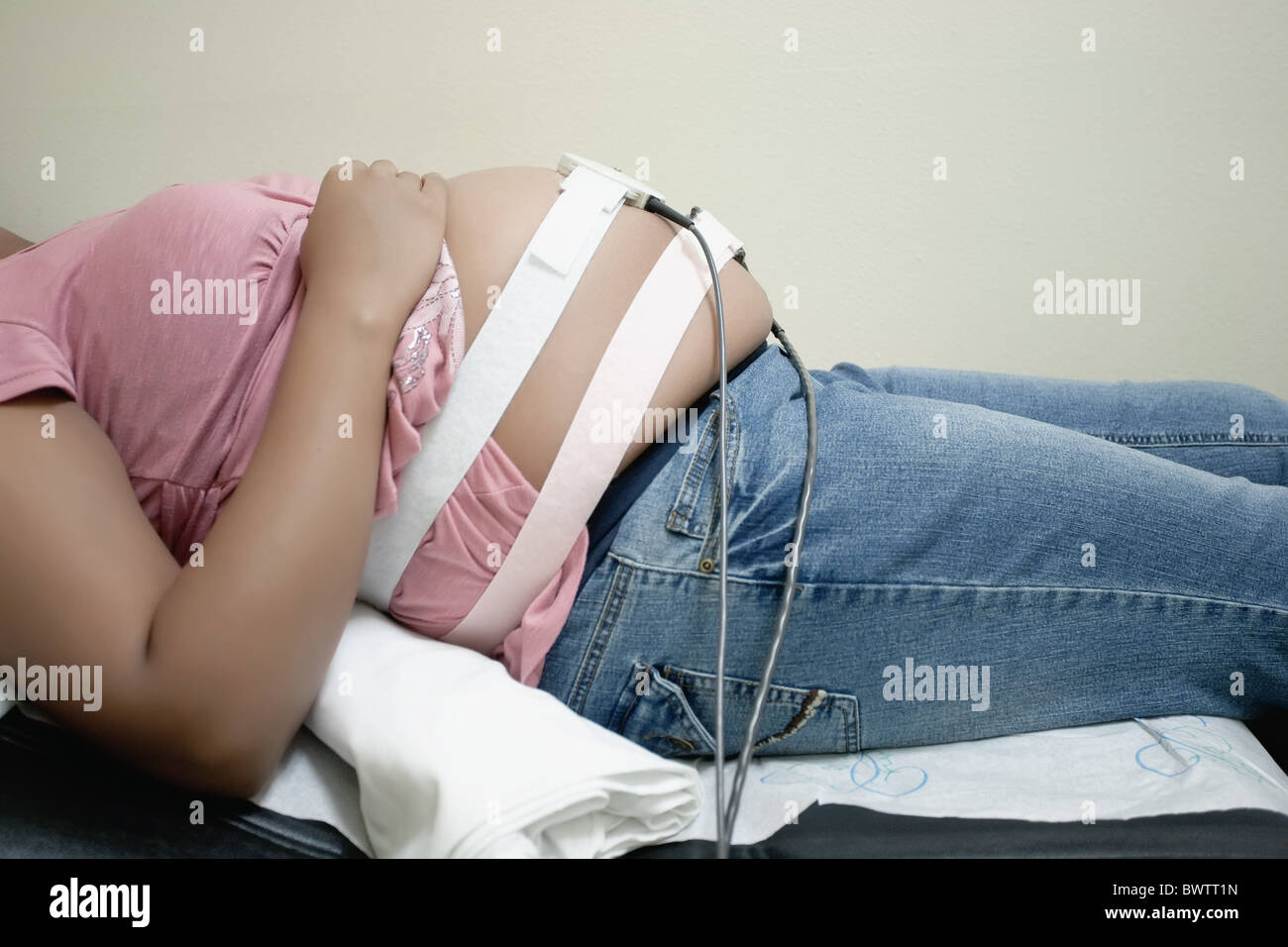 pregnant mother having baby monitor examination and laying down at doctor's office - Stock Image