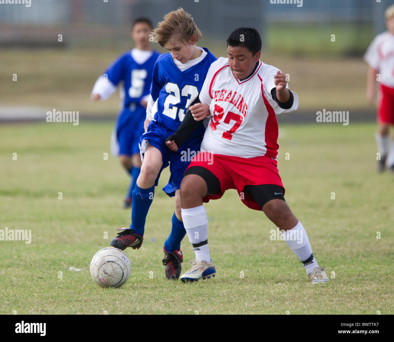 Seventh and eighth grade boys ages 13 and 14 play soccer for their school teams in a league match in Austin, Texas - Stock Image