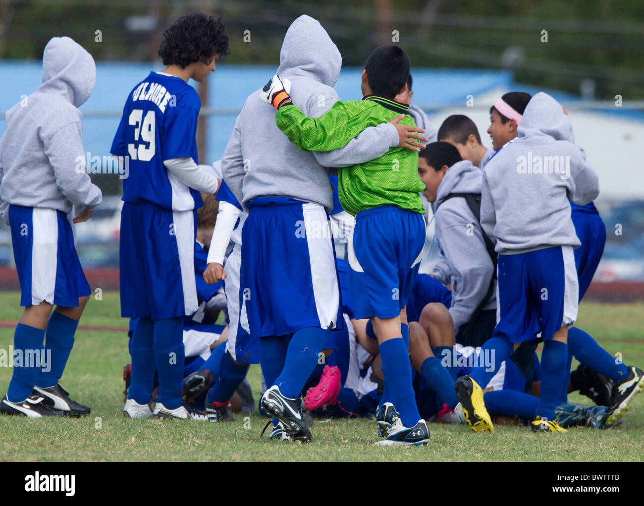 Middle school boys soccer team members huddle to stay warm during timeout of game on chilly morning in Austin, Texas - Stock Image