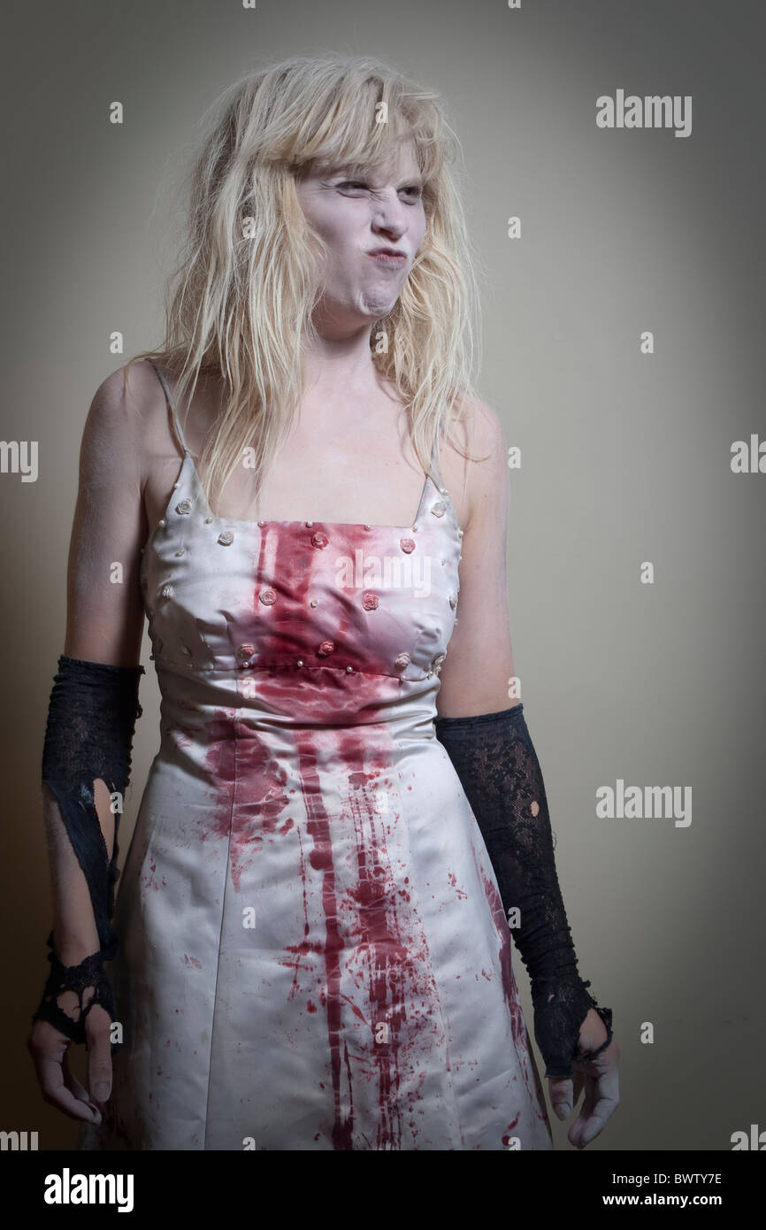 blond woman in zombie costume makes funny face - Stock Image