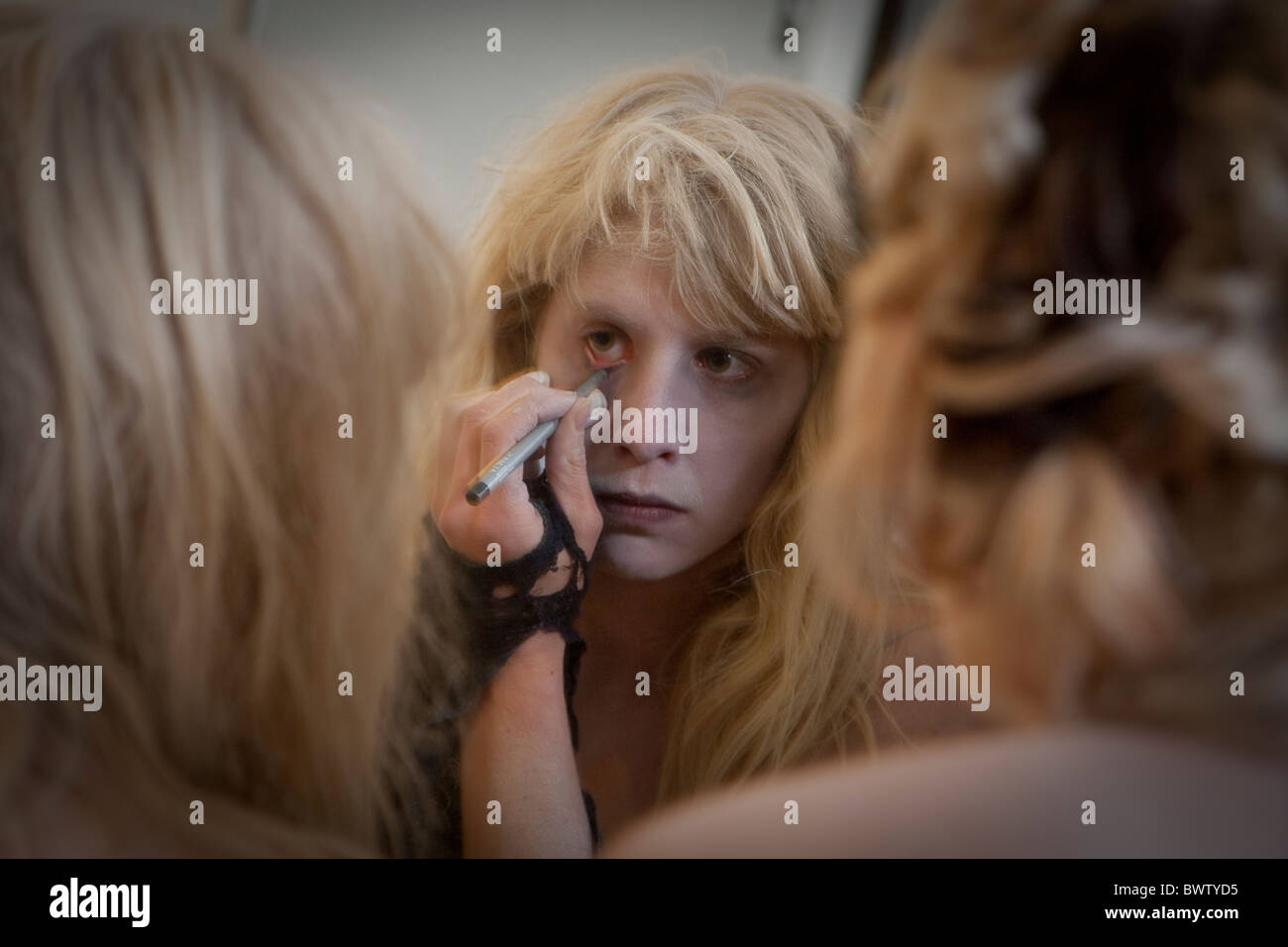 zombie girl does Halloween make-up in mirror - Stock Image
