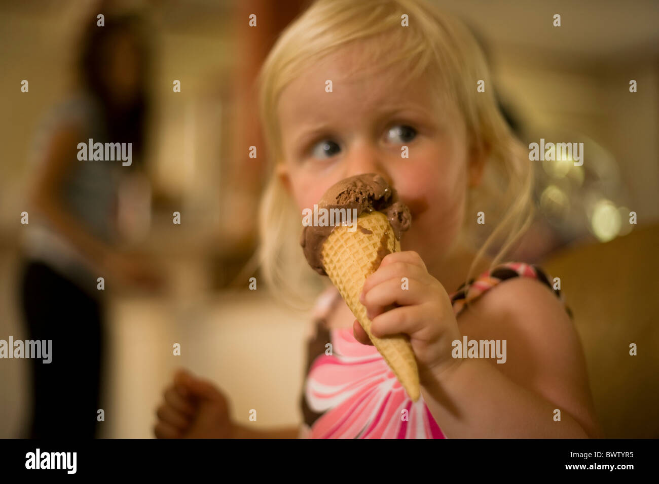 little blond girl eats chocolate ice cream in a cone - Stock Image