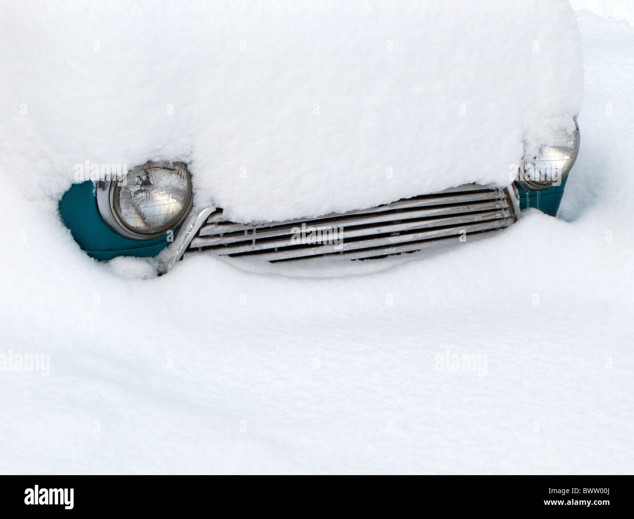 Car Grille and Headlamps poking through heavy snow - Stock Image