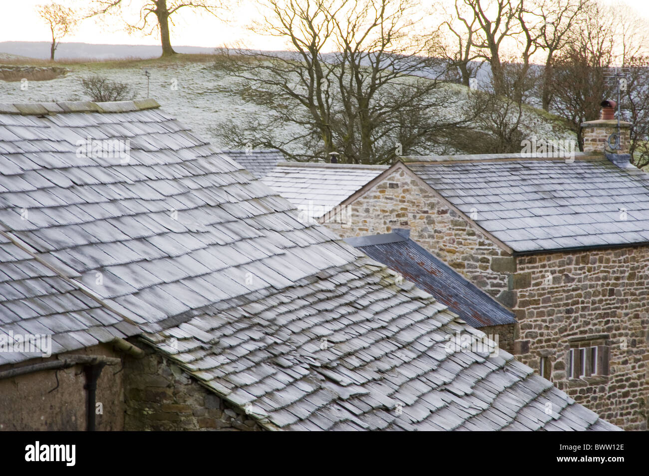 Frost slate roofs farm buildings Cumbria England - Stock Image