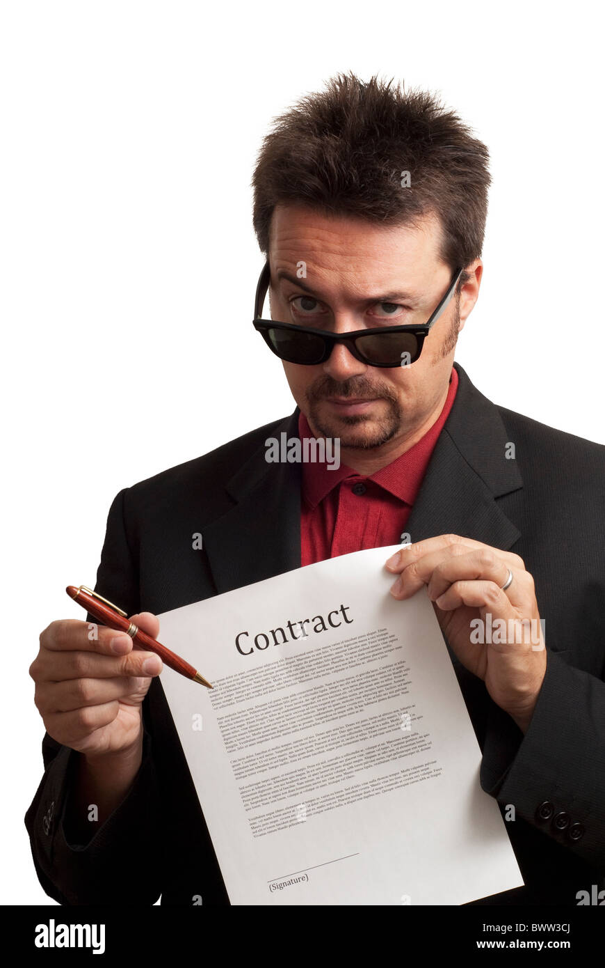 Shady and untrustworthy business man offering pen to sign a contract. Studioshot on white background - Stock Image