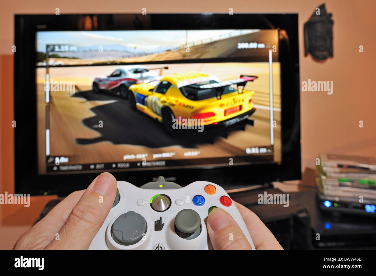 Hands holding controller in front of television screen showing cars in racing game - Stock Image