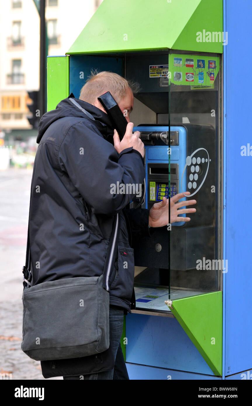 Man using a public telephone - Stock Image