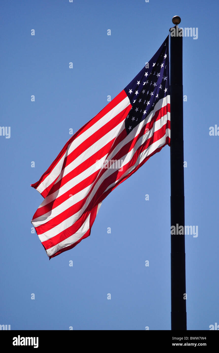 American flag blowing against blue sky - Stock Image