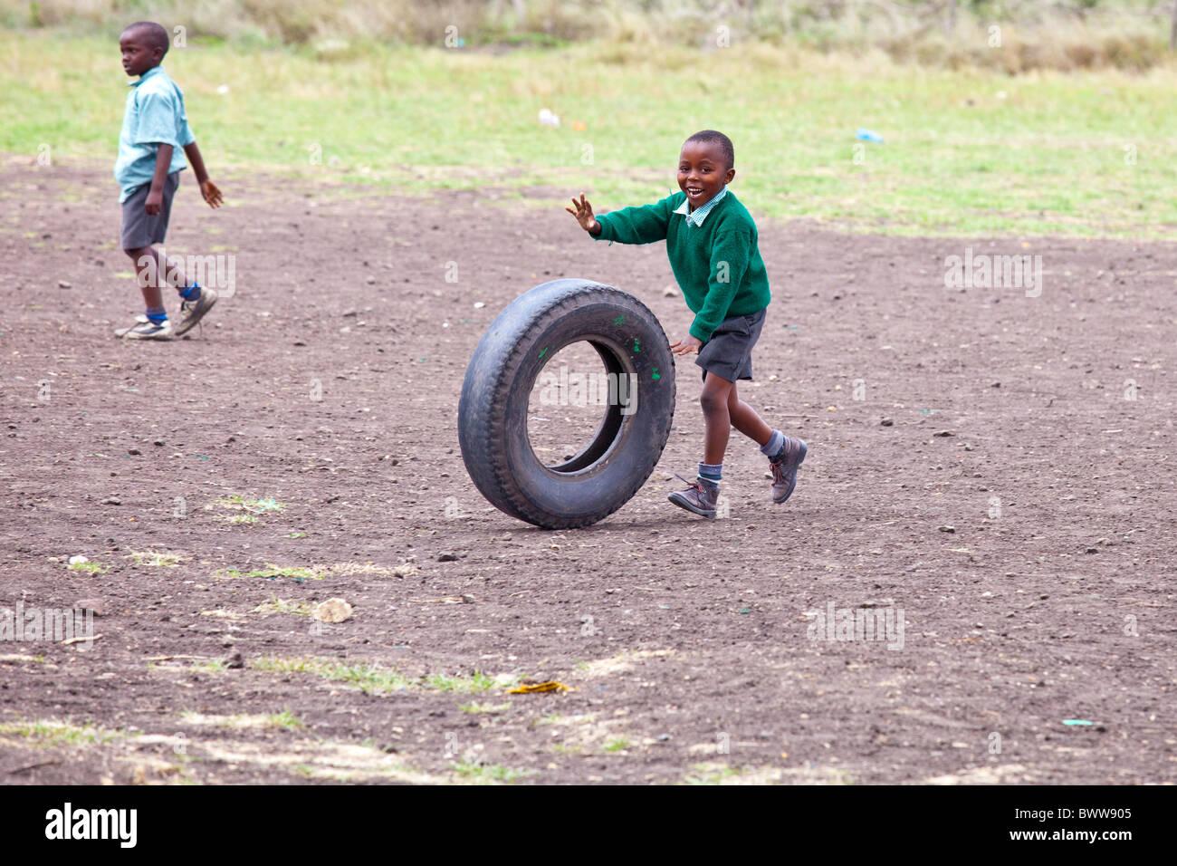 Boy rolling a tire, Maji Mazuri Centre and School, Nairobi, Kenya - Stock Image