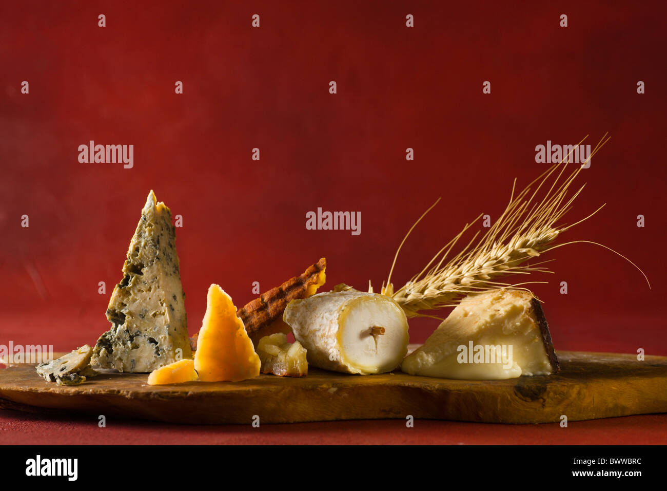 A wood cuttingboard with, from left to right: Cabrales (Cow - Spain), Roomano (Cow - Holland), Majorero Pimenton (Goat - Canary Stock Photo