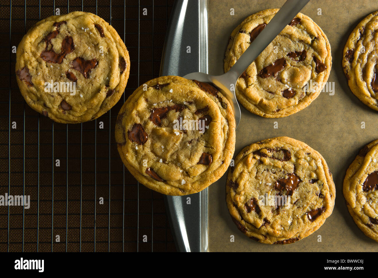 A Spatula removing a Chocolate Chip Cookies from a baking sheet over a brown linen table cloth and a wire cooling rack. Stock Photo