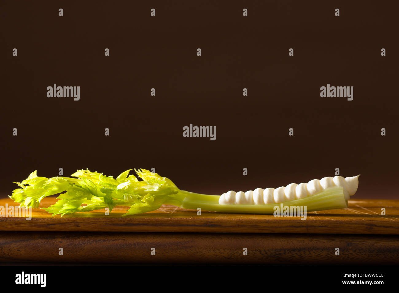 A stalk of celery heart with cream cheese piped in it's cavity over a wood board. - Stock Image