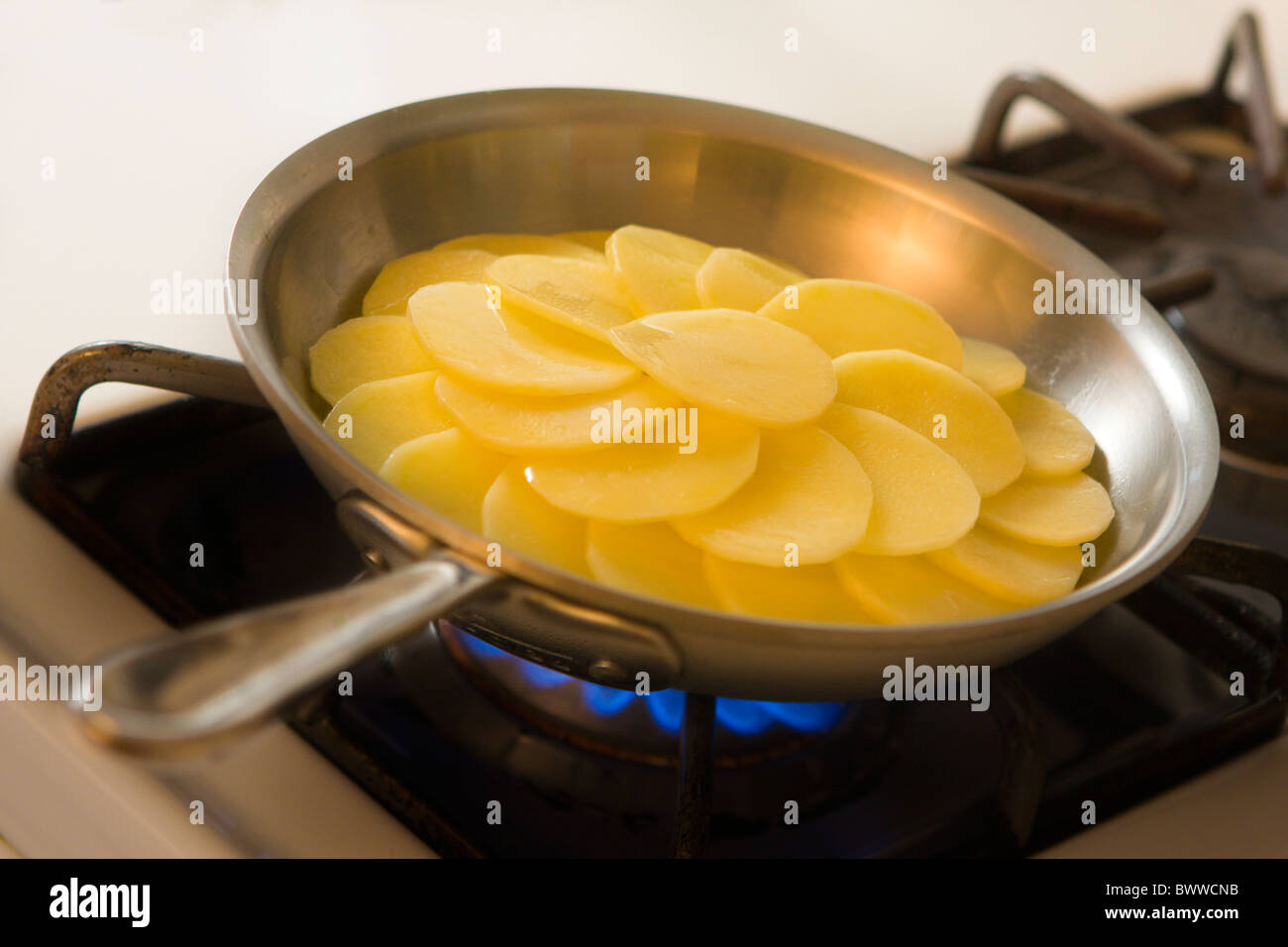 The various steps of preparing potatoes Anna using a brushed aluminum sauteuse with stainless steel lining. - Stock Image