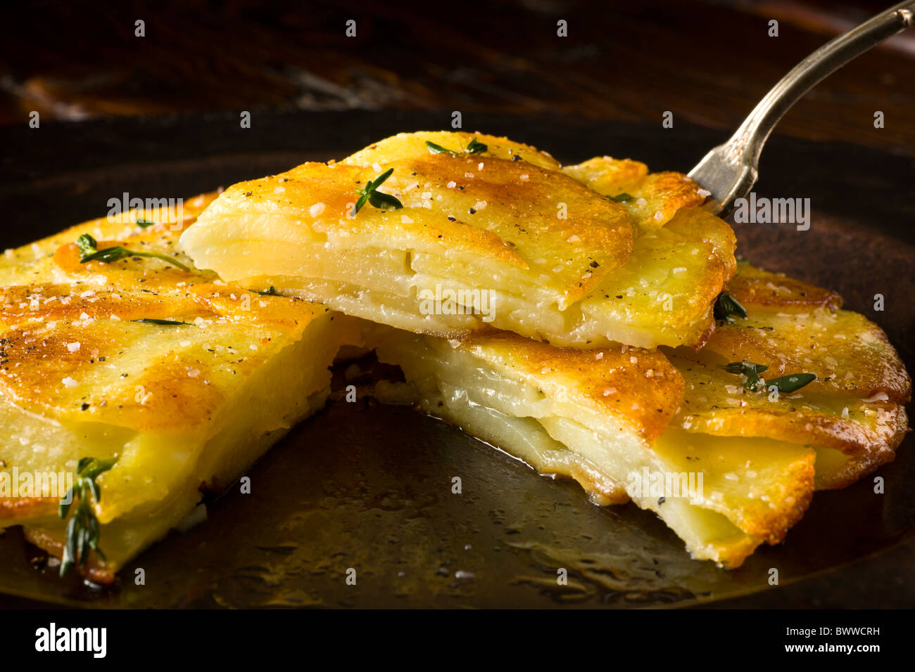 Potato Galettes or Anna garnished with fresh thyme, salt and pepper and served on a rustic plate. Stock Photo