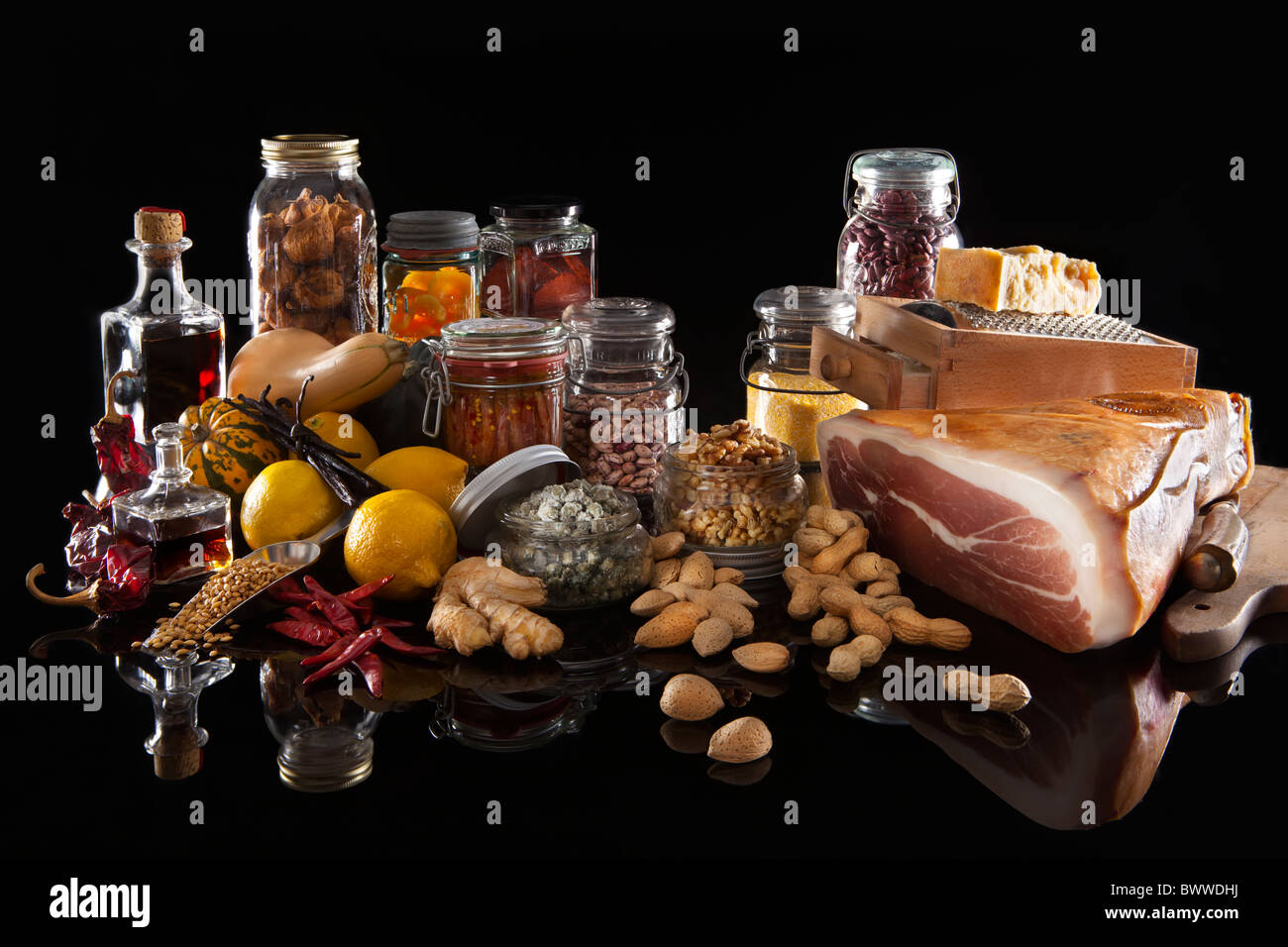 A variety of pantry food in various glass jars and bottles on black background - Stock Image