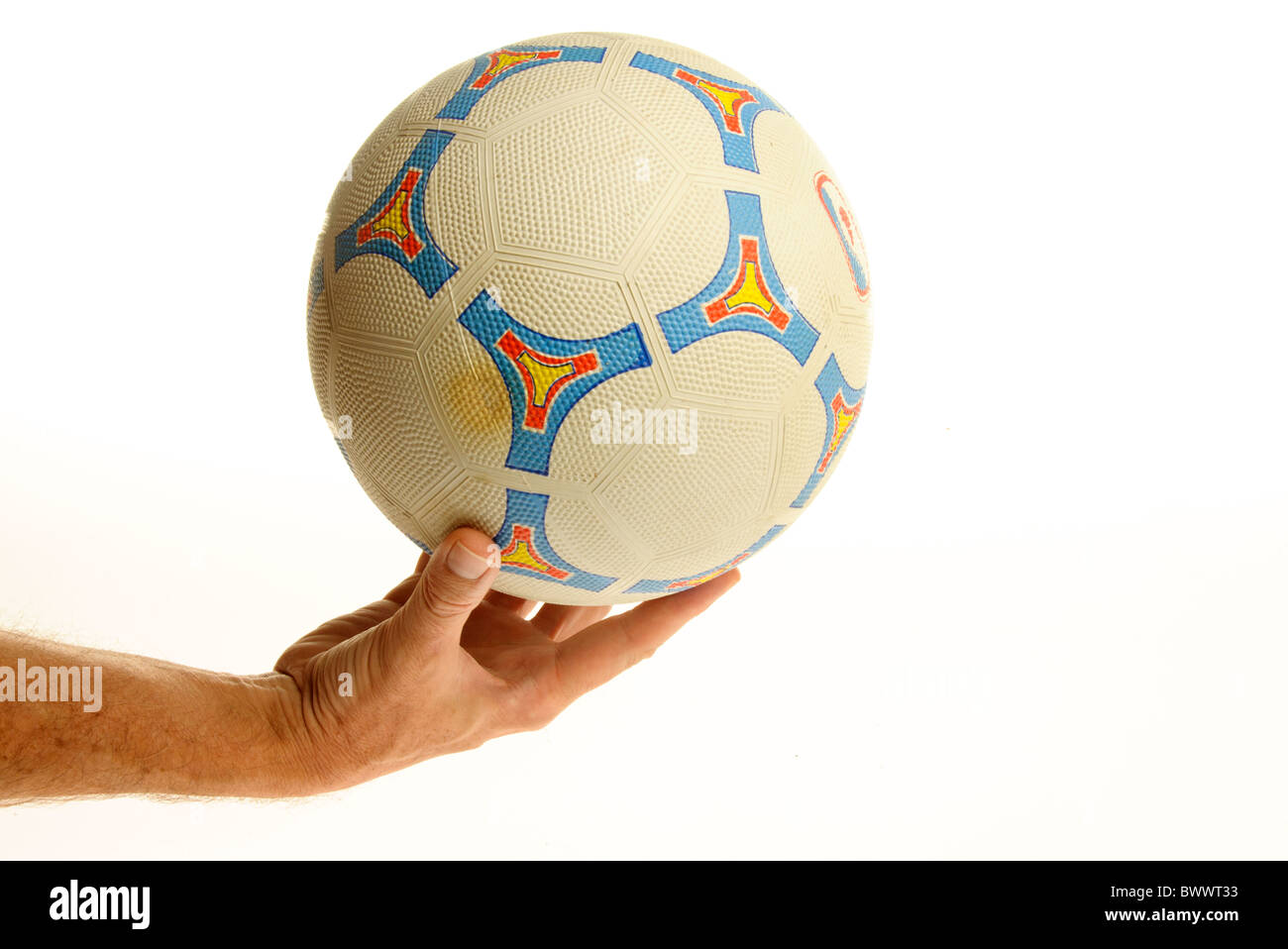 hand holding a football - Stock Image