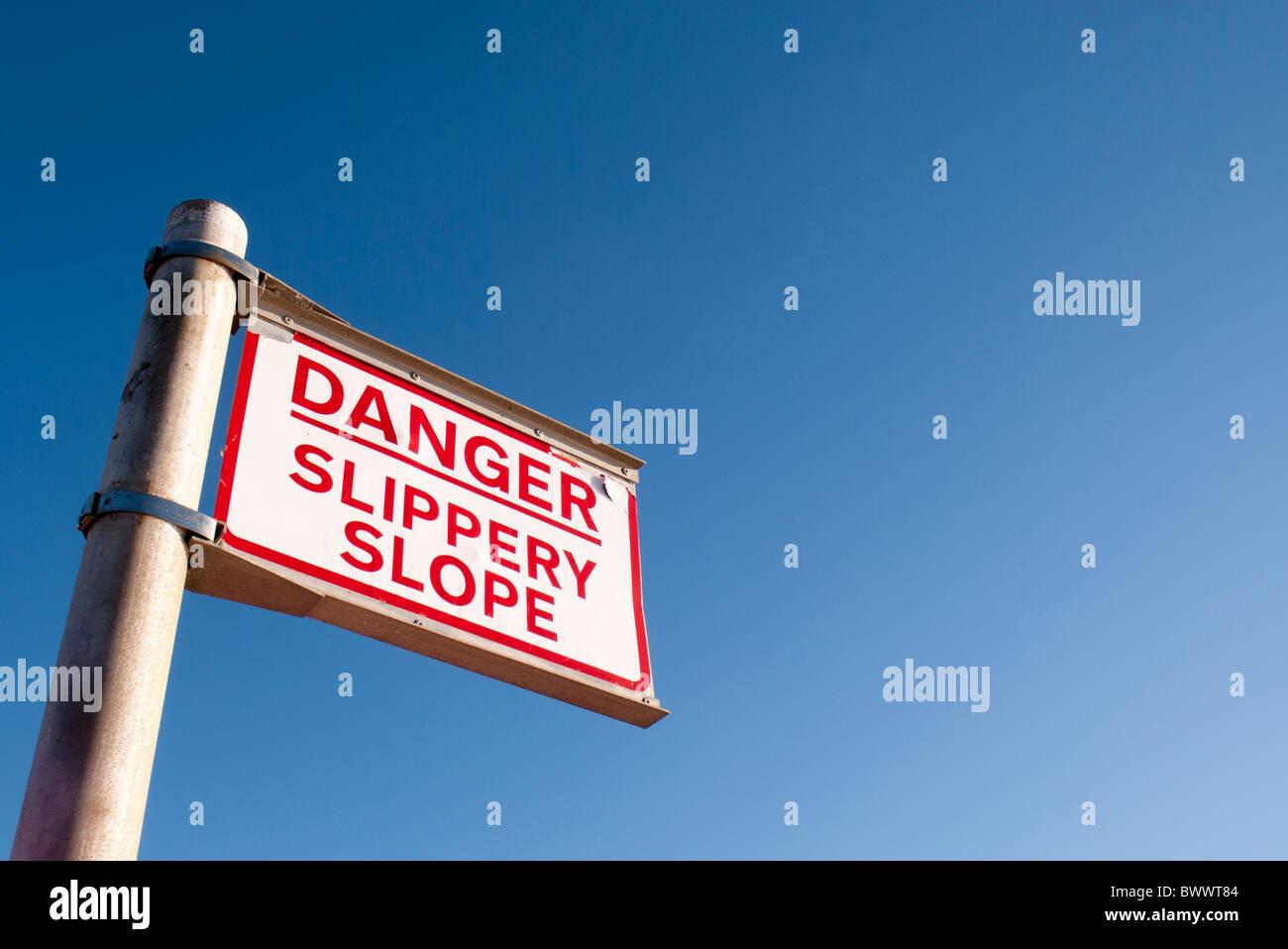danger slippery slope sign post - Stock Image
