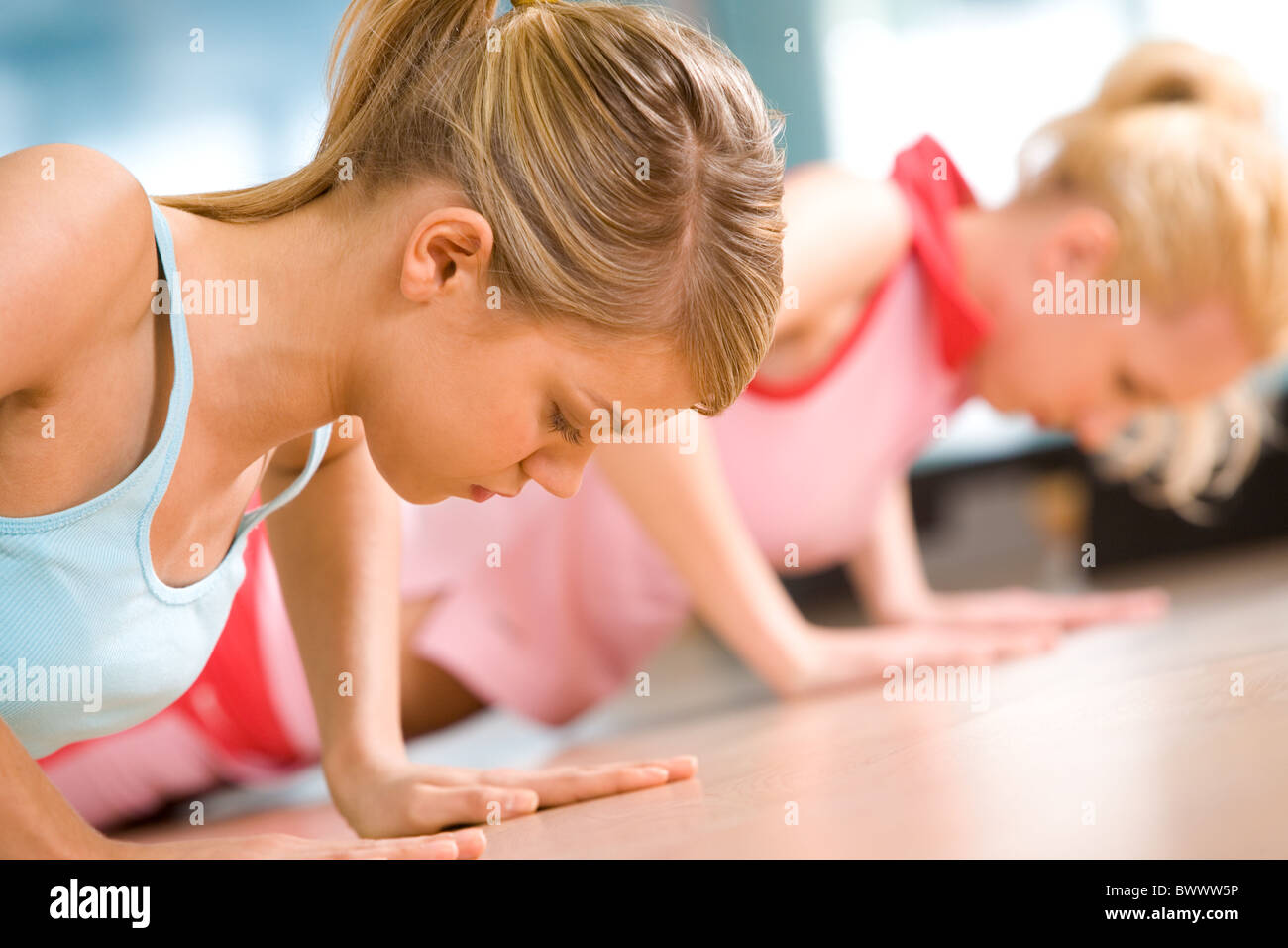Photo of young girl doing difficult exercise for arm biceps on the floor - Stock Image