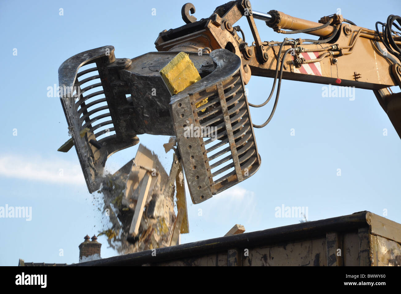 Demolition machinery in action dropping building materials - Stock Image