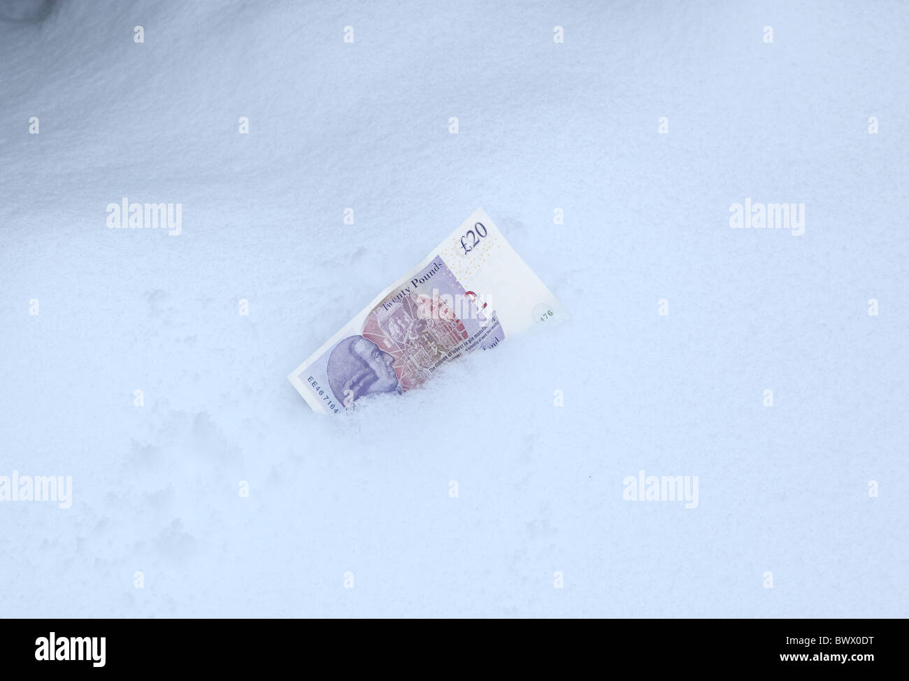 £20 note lying on the snow - Stock Image