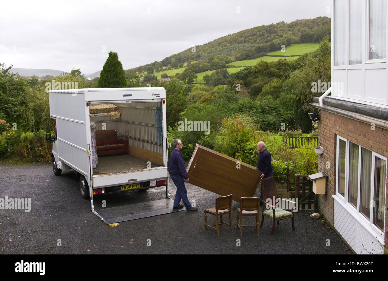 Two men removing furniture from a rural house for a community recycling project in Newtown Powys Mid Wales UK Stock Photo
