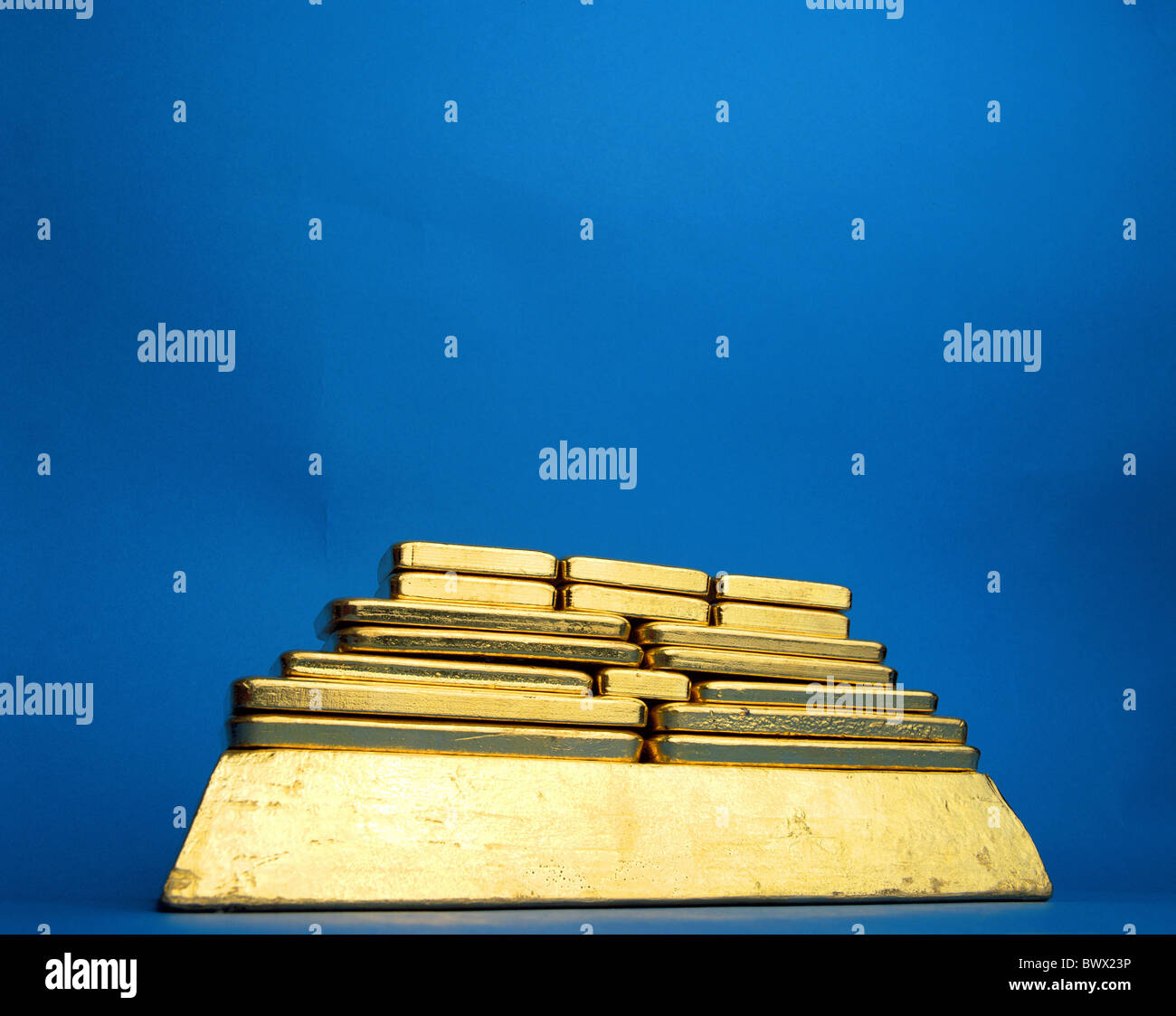 stacked up piled up money gold bank blue background gold bar pyramid - Stock Image