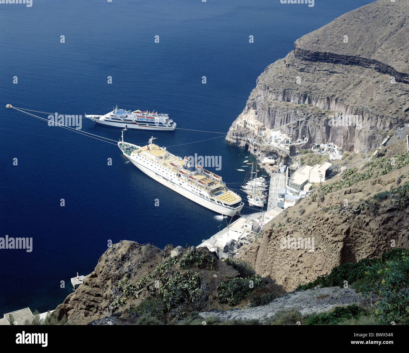 ferries ferryboats Thira Fira Greece harbour port cliffs Cyclades Santorini overview holidays travel - Stock Image