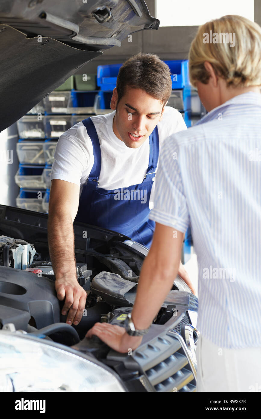 mechanic talking with female client in auto repair shop. - Stock Image