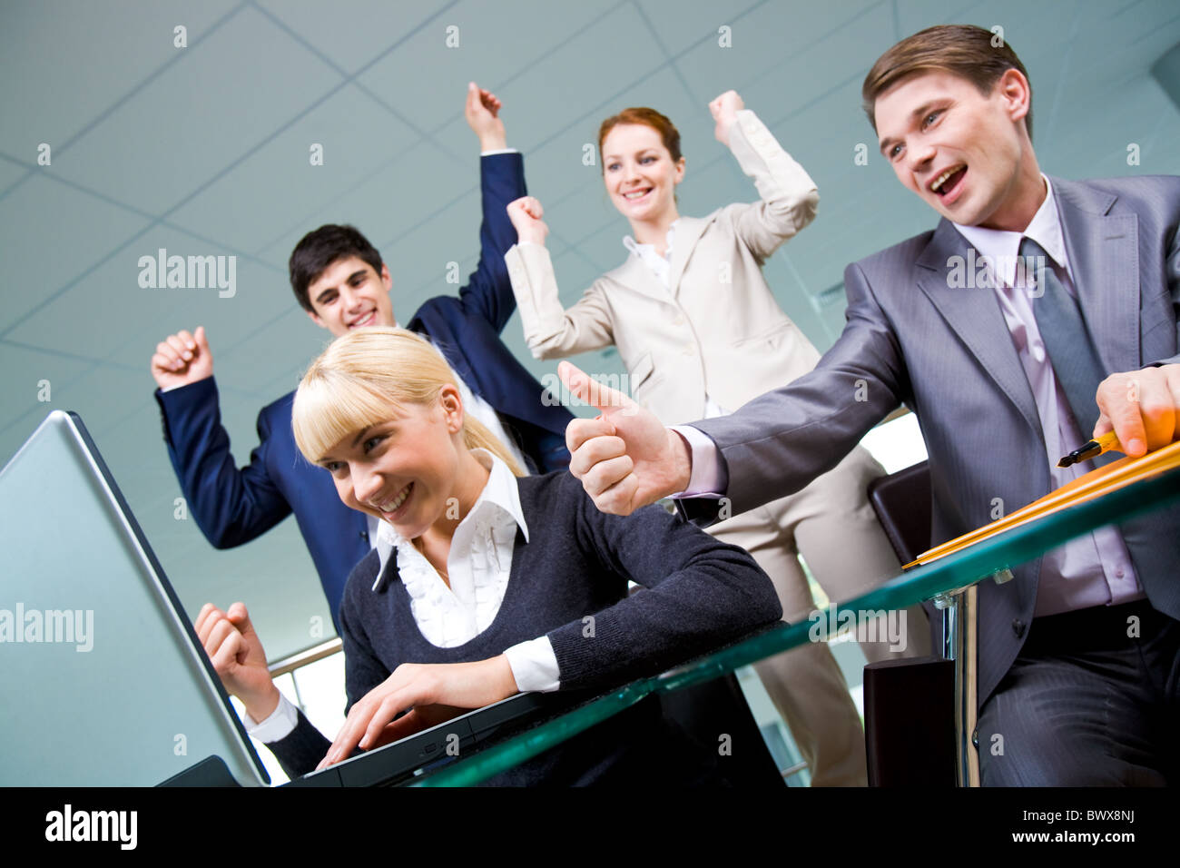 Group of happy partners looking at laptop monitor with expression of gladness - Stock Image