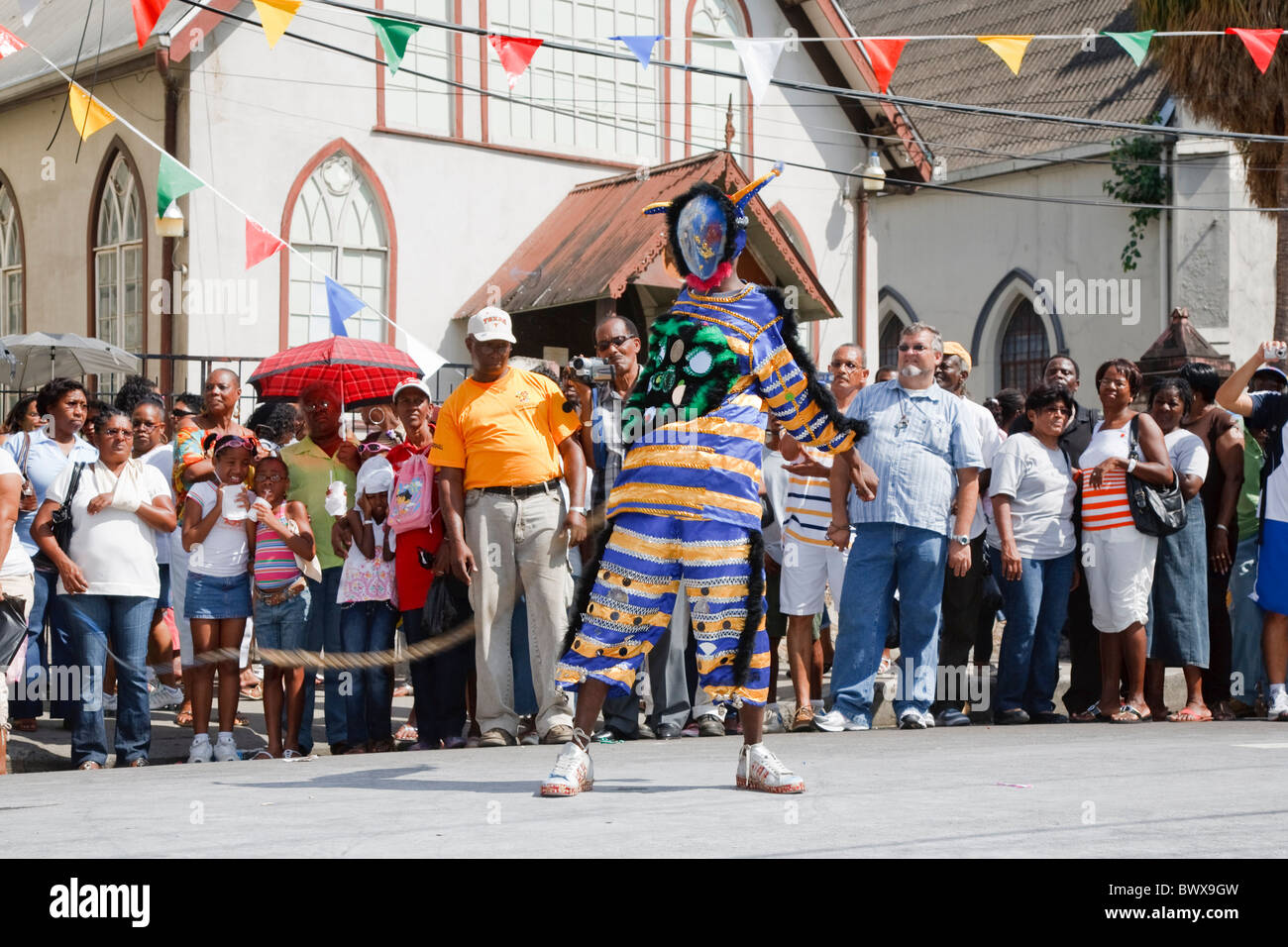Junior traditional Mas parade - jab jab with whip performs for the crowd - Stock Image