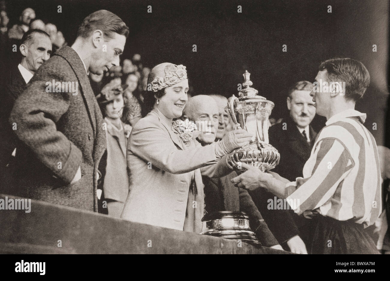 King George VI and Queen Elizabeth presenting the cup to Raich Carter, the Sunderland captain after his teams victory - Stock Image