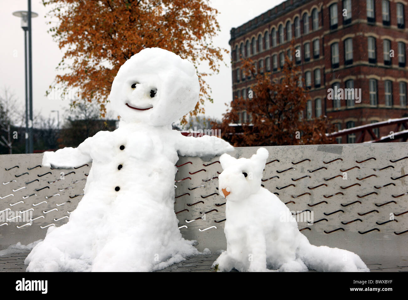 Snowman and dog sitting on a park bench - Stock Image