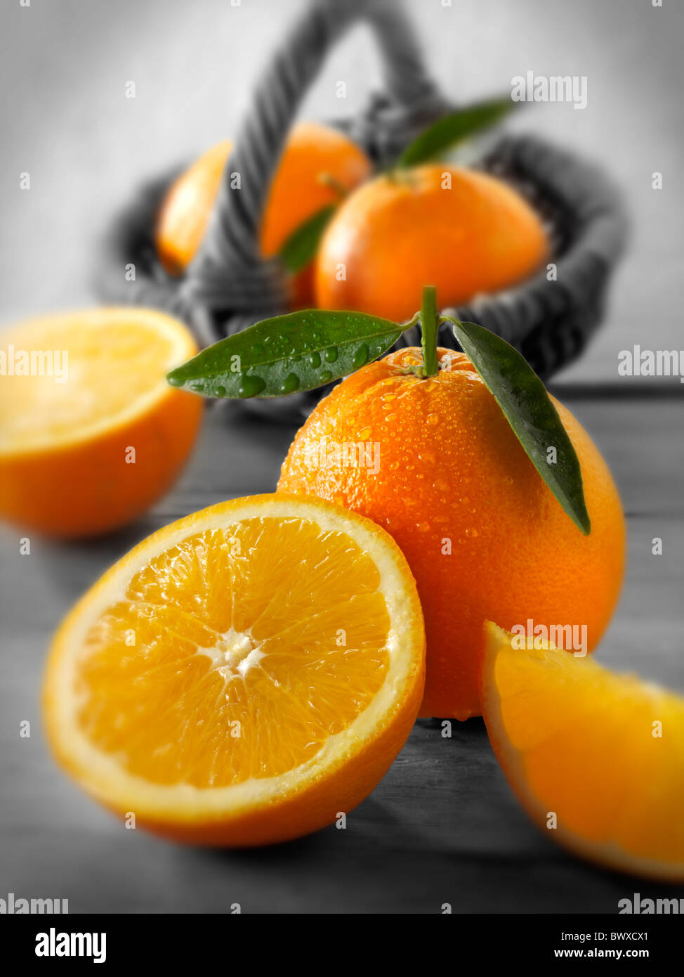 Fresh oranges whole and cut halves with leaves in a kitchen setting Stock Photo