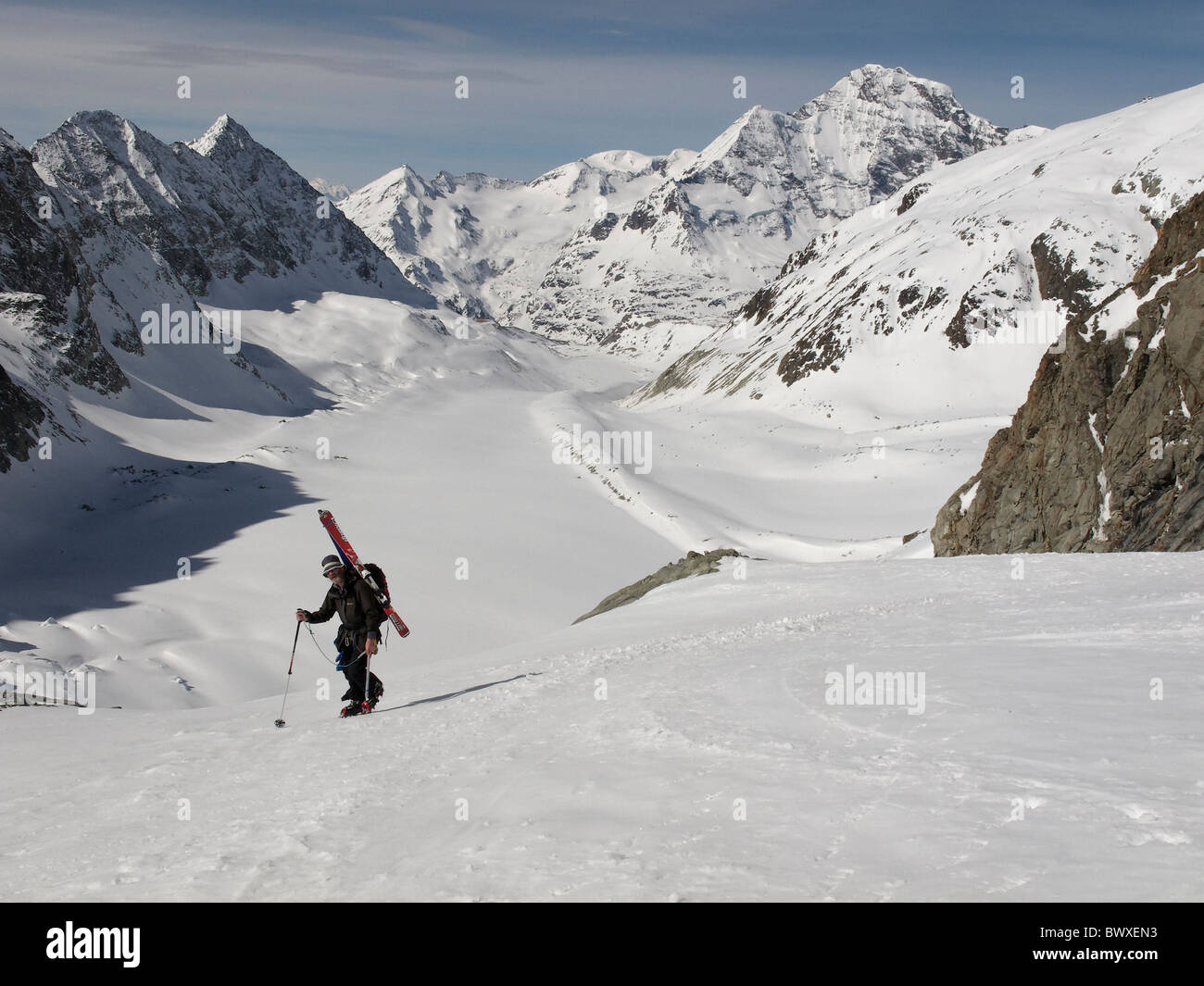 A ski tourer walking up the steeper section at the side of the Brenay icefall, on the Brenay Glacier, Switzerland - Stock Image