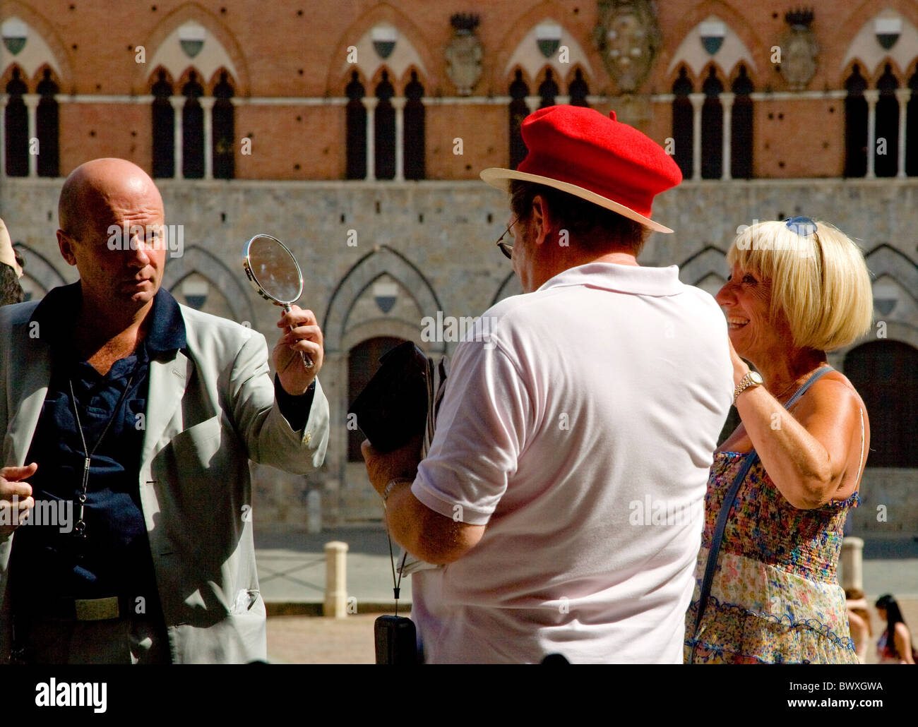 Street performer reveals his red beret plonked on an innocent tourist's hat in the Campo of Sienna Tuscany Italy - Stock Image