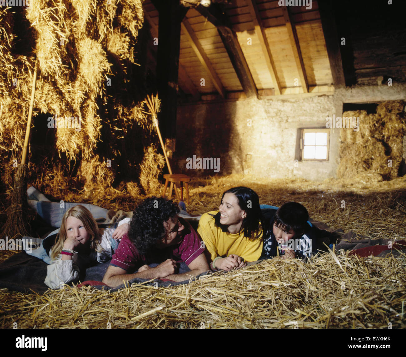 farm family holidays spare time hayloft in straw recumbent sleeping straw canton Jura Switzerland Europe - Stock Image