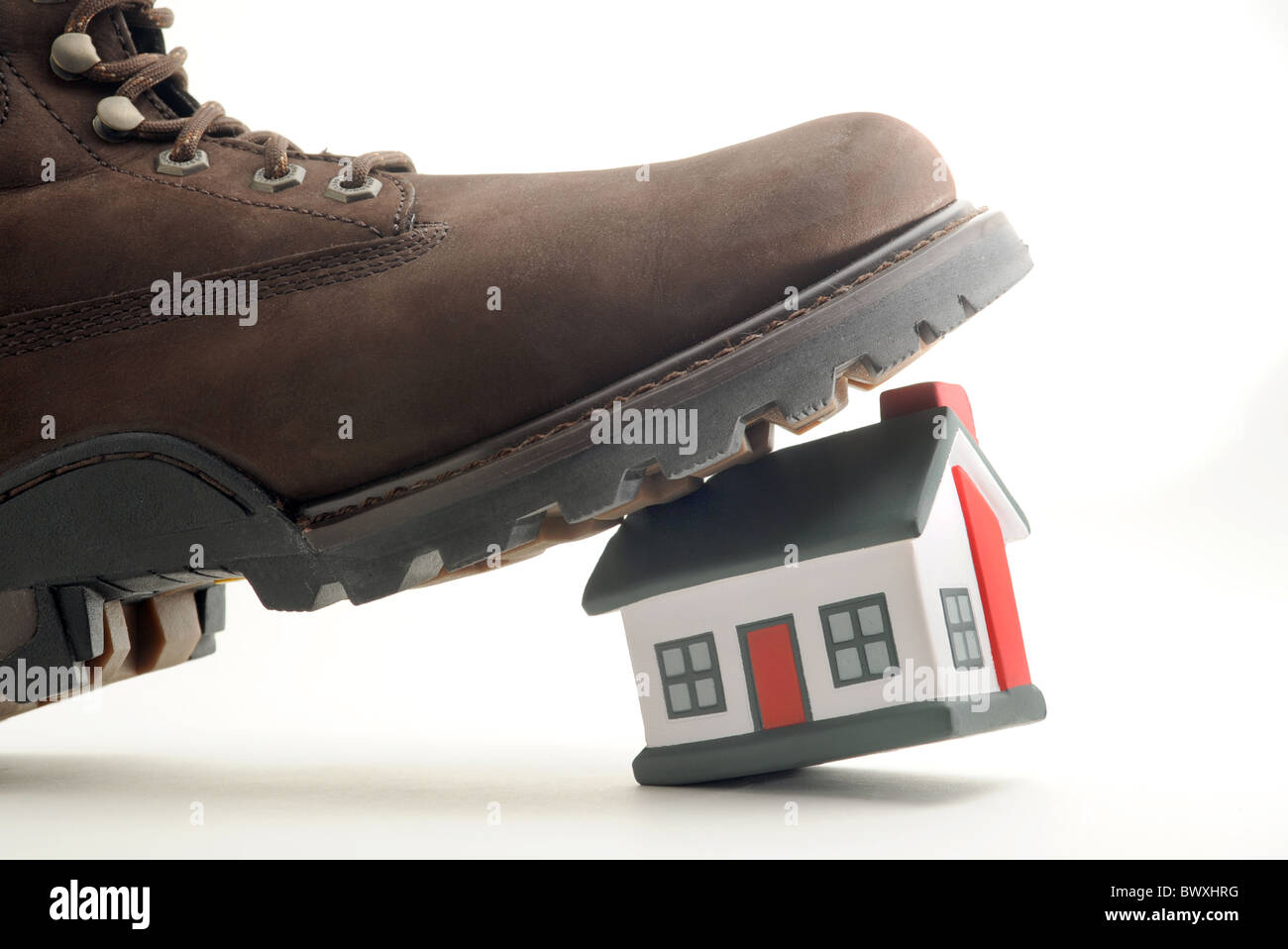 HOUSE BEING TROD ON BY MANS BOOT RE HOUSING MARKETS MORTGAGES PRICES ETC UK - Stock Image