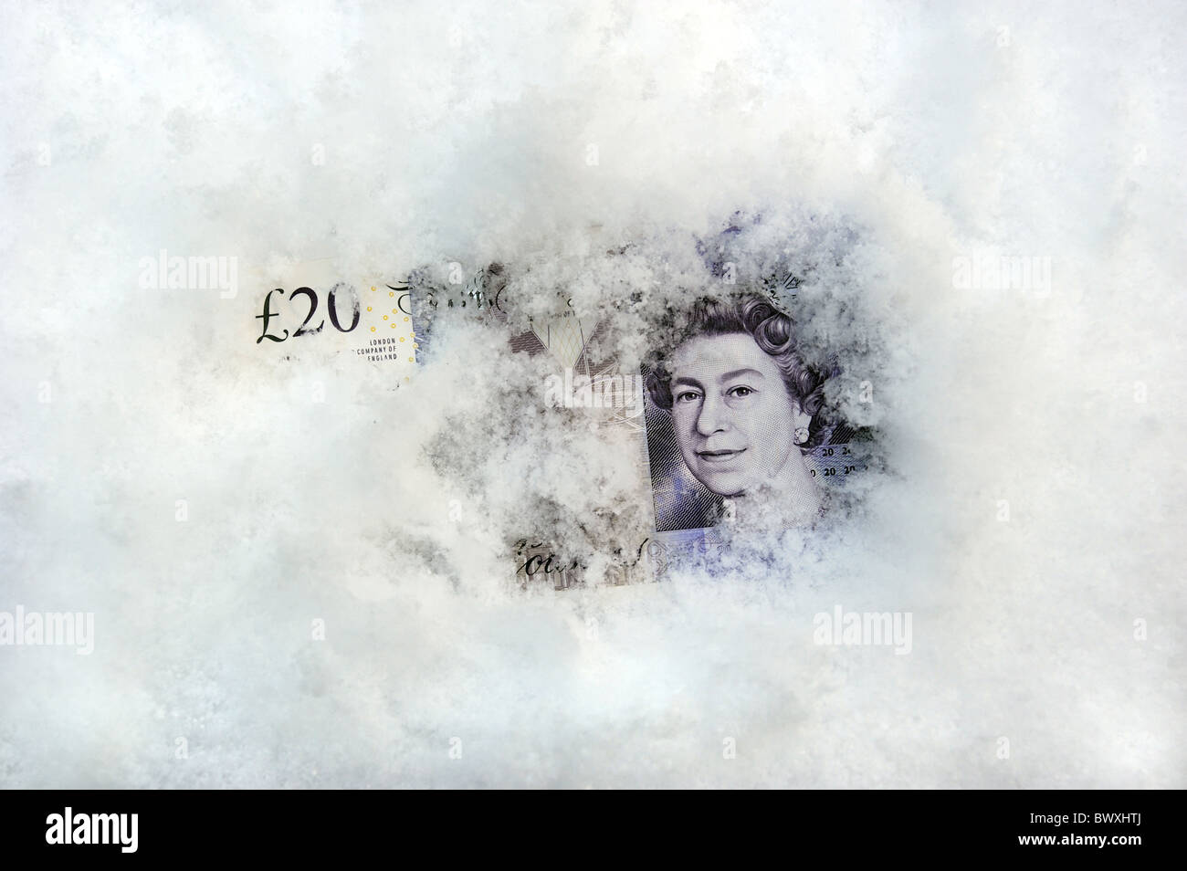BRITISH TWENTY POUND NOTE IN SNOW AND ICE RE WINTER FUEL PAYMENTS SAVINGS CASH MONEY INVESTMENTS MORTGAGES ETC - Stock Image