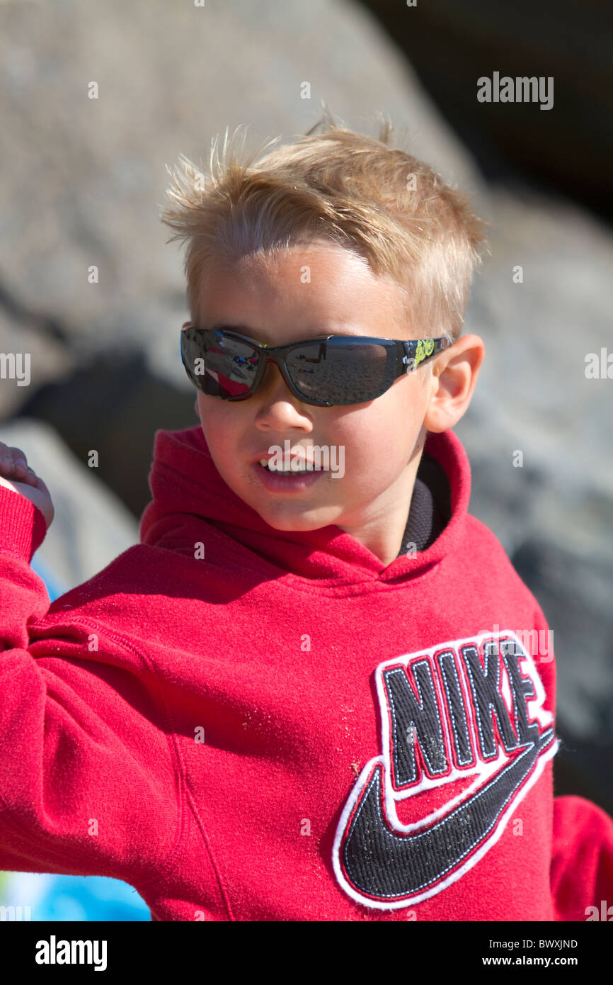 Boy wearing sunglasses for ultraviolet protection along the D River in Lincoln City, Oregon, USA. - Stock Image