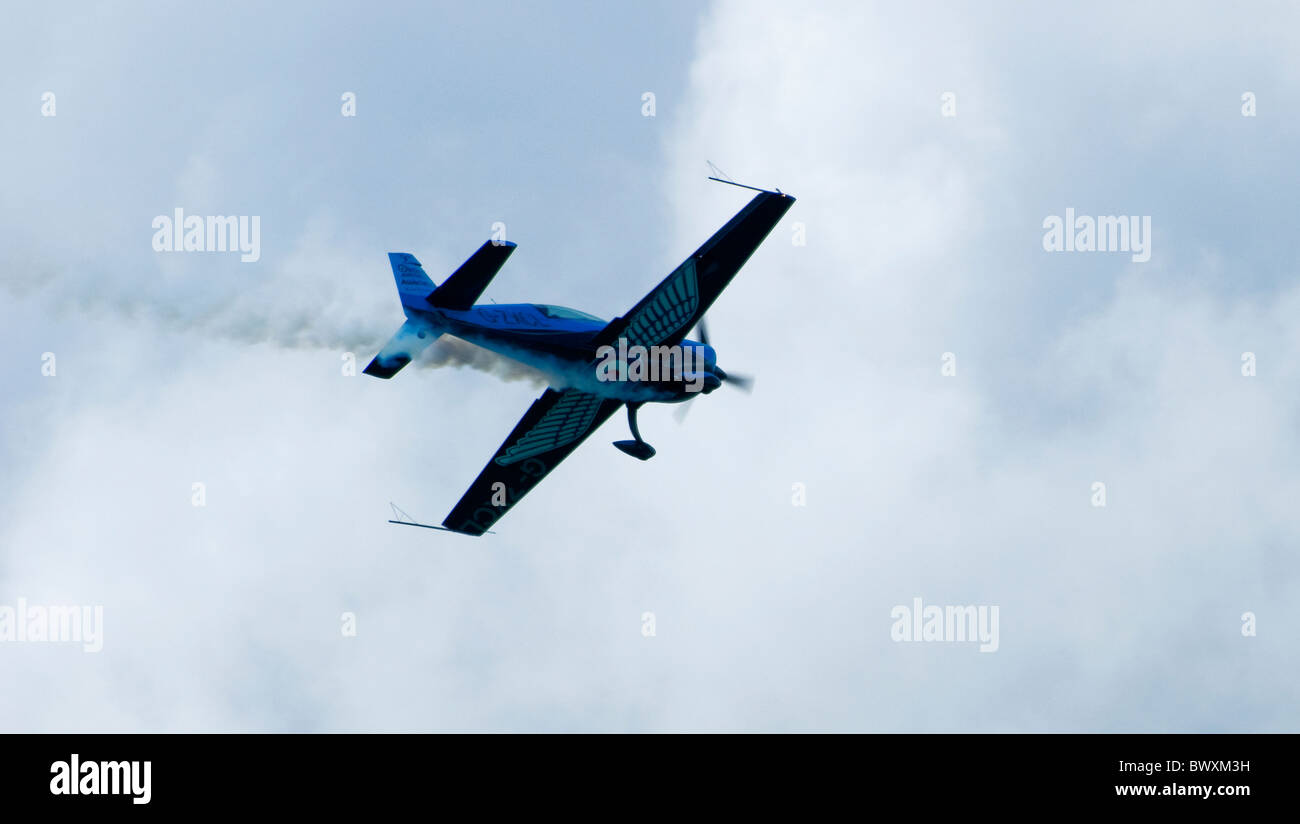 A Blades Blade extra 300 display plane flying left to right with smoke trailing - heading towards clouds - Stock Image