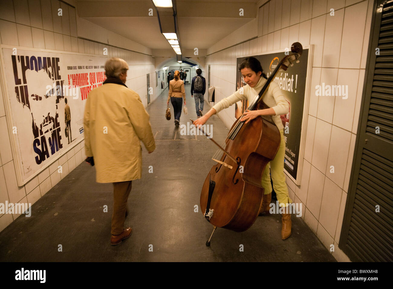 A female busker playing classical music on a double bass in the metro, the Louvre, Paris France - Stock Image