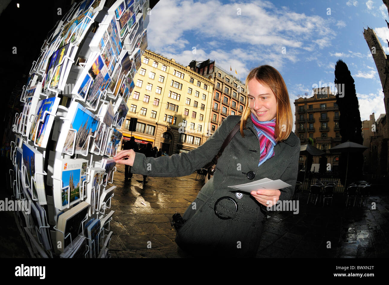 Young Woman Selecting Postcards, Barcelona, UK - Stock Image
