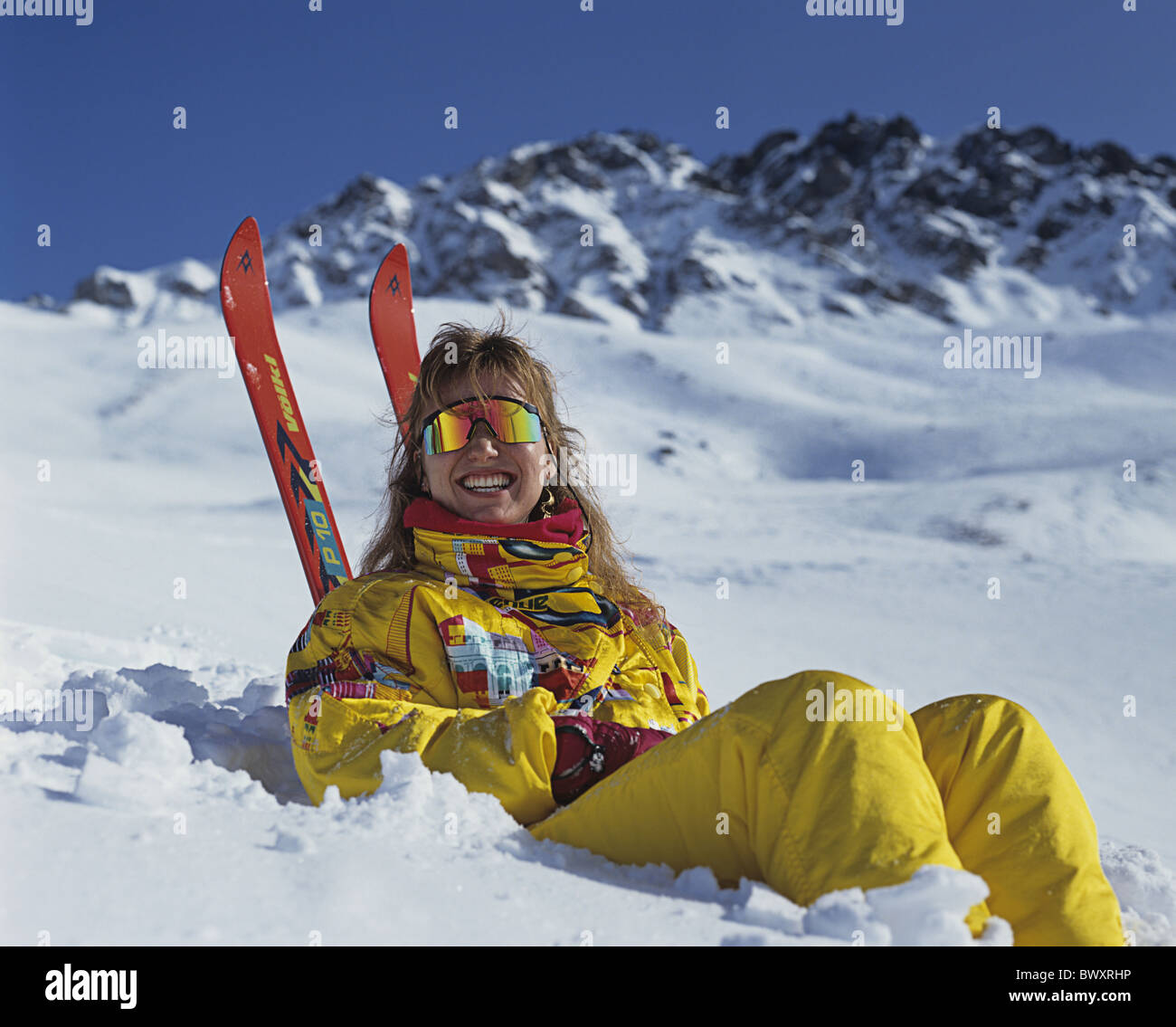 woman laugh lie slope take it easy relax skier ski skiing winter sports sport sunglasses winter - Stock Image