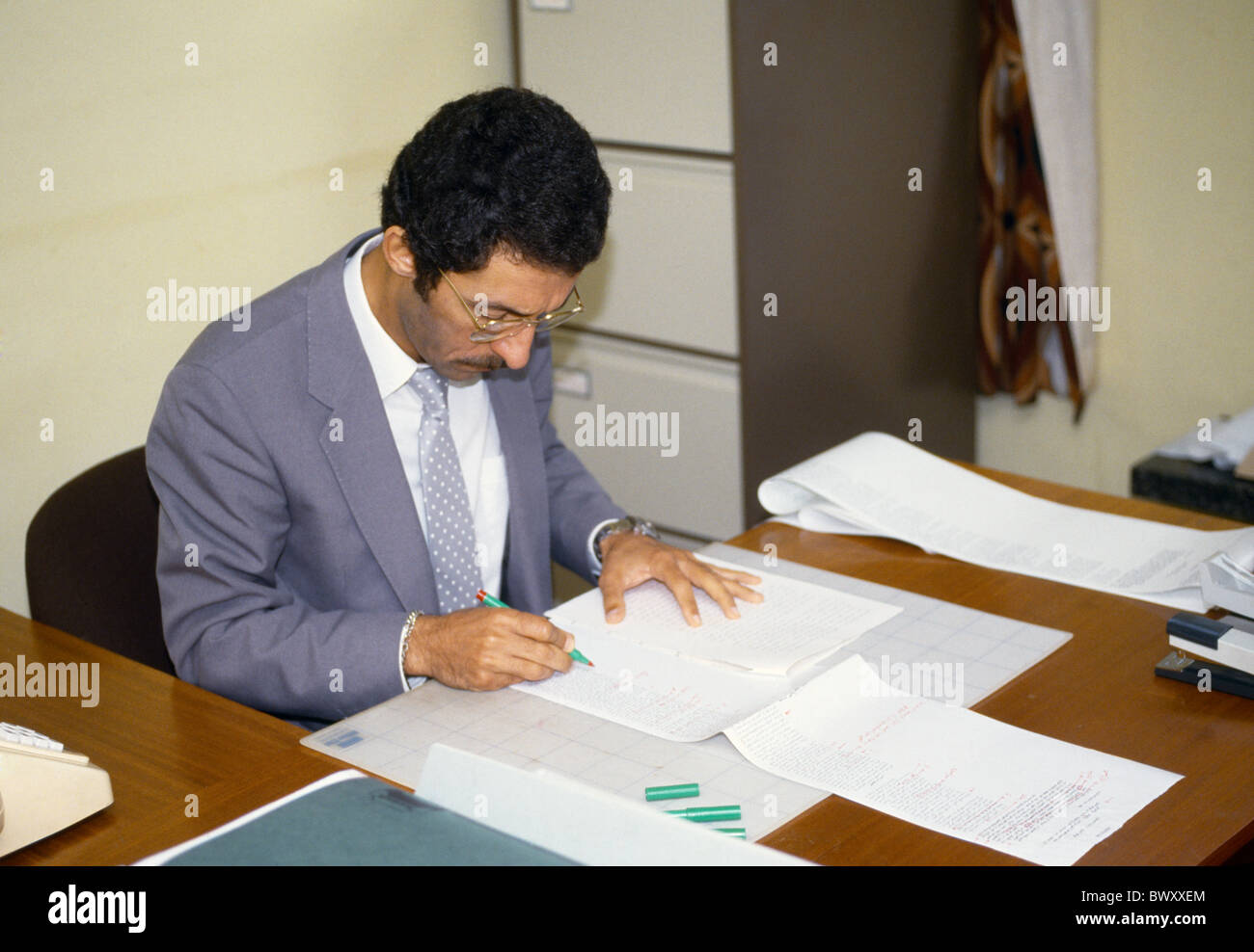 Egyptian Proof Reading Arabic Manuscript Inside Office Signing Papers - Stock Image