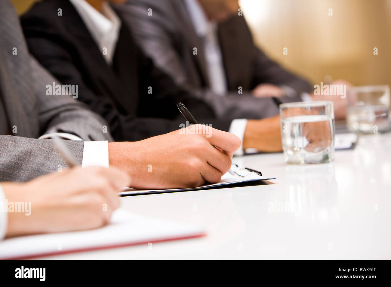 Close-up of hands with pens making notes during conference - Stock Image