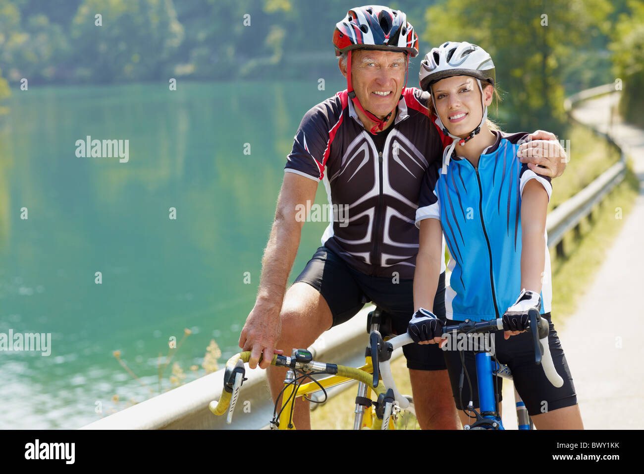 Senior man and young woman on road bike. Copy space - Stock Image