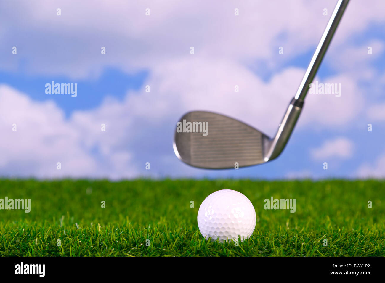 Surface level photo of an iron golf club in mid swing about to hit a ball on the fairway. - Stock Image