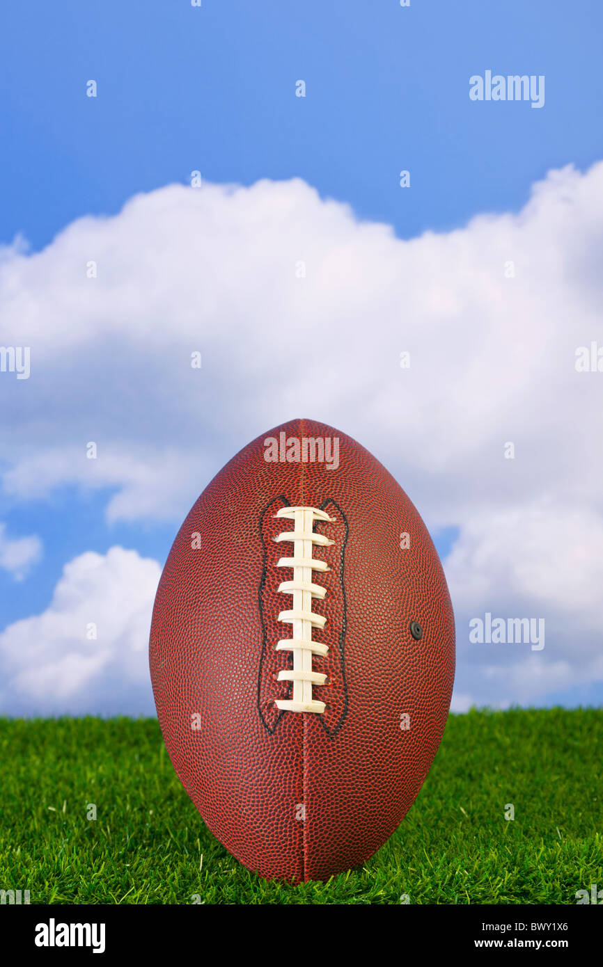 Photo of an American football tee'd up on the grass - Stock Image