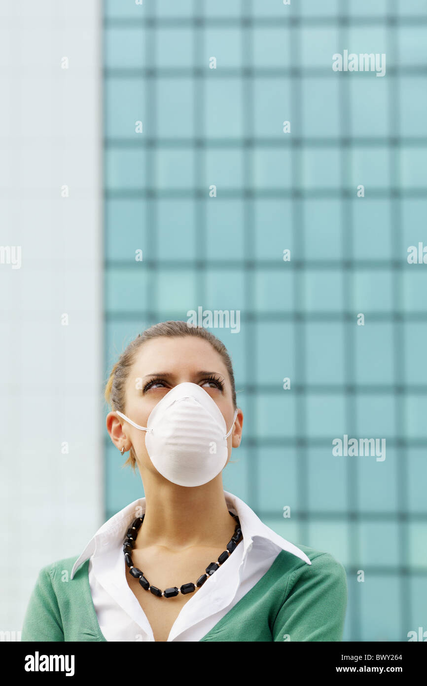 woman standing against office building and wearing protective mask. Copy space - Stock Image