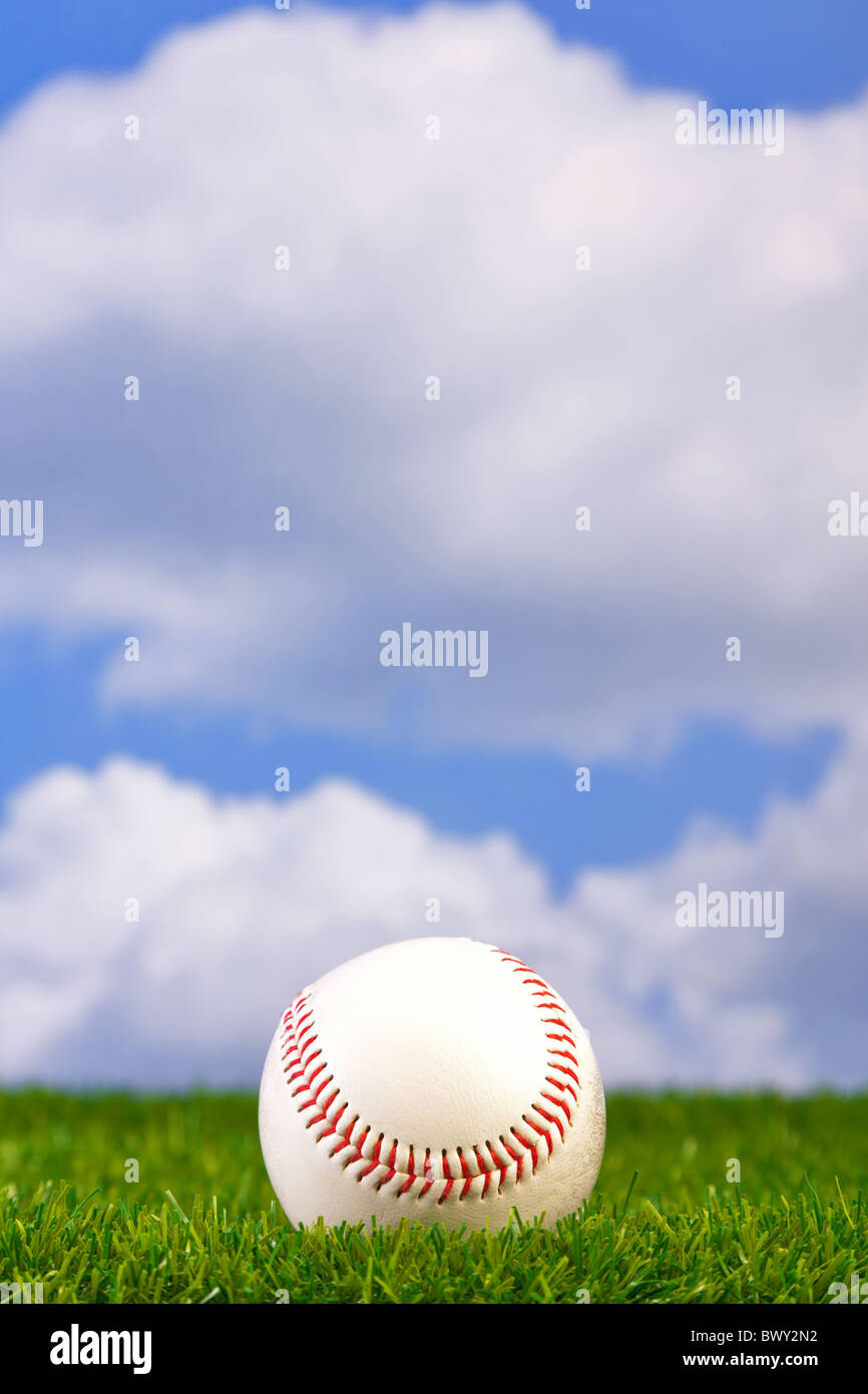 Photo of a baseball on grass with sky background. - Stock Image